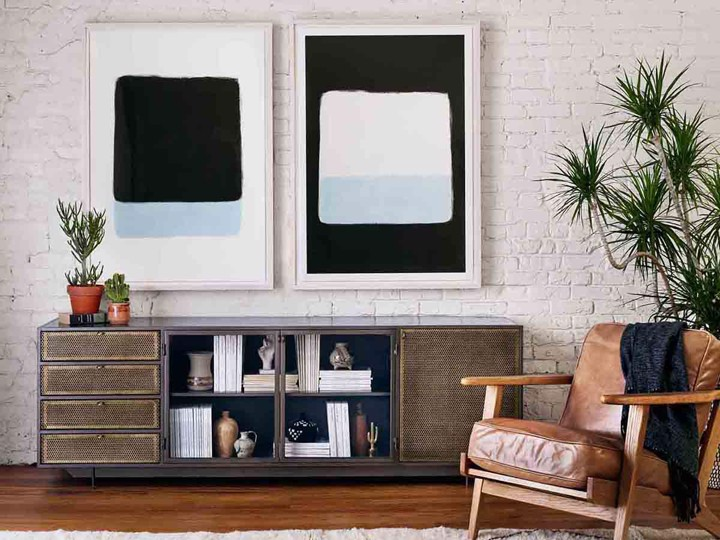 Mid-century modern leather arm chair, with simple wall art and a console
