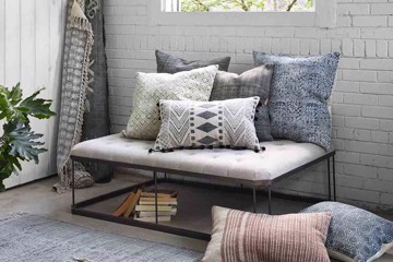 four hands pillows stacked on a tufted bench