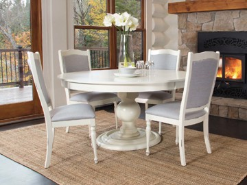 White wooden pedestal base circular dining table with white and grey upholstered dining chairs