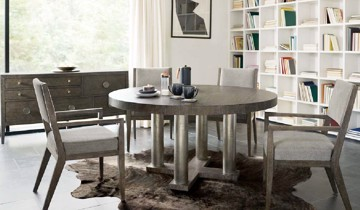 Modern metallic finish pedestal dining table with grey wooden and upholstered dining arm chairs