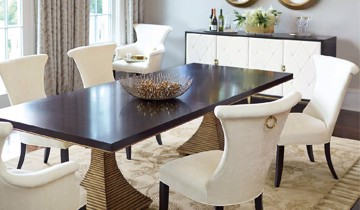 White upholstered dining arm and side chairs with wooden pedestal dining table