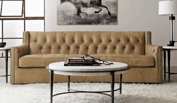 Tan upholstered tufted sofa with round cocktail table