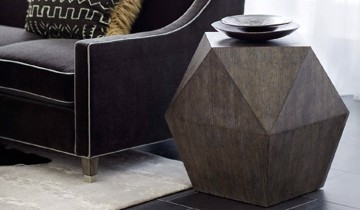 Geometric end table and black upholstered sofa with white welt.