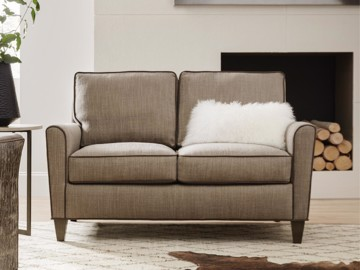 Beige upholstered loveseat with contrasting welt