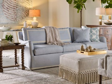 Blue upholstered sofa with upholstered cocktail table and wood end table