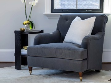 Dark grey upholstered tufted chair with black side table