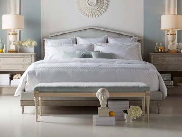 Natural wood upholstered bed with upholstered bench and ivory side tables