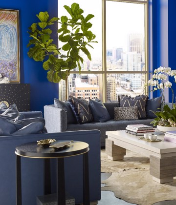 grey upholstered sofa with blue arm chair and cocktail table