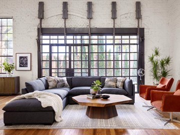 dark grey upholstered sectional with leather club chairs and hexagonal cocktail table