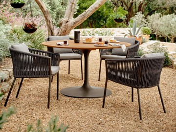Woven outdoor arm chairs with modern pedestal table