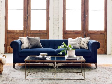Blue upholstered Chesterfield sofa with glass and metal cocktail table