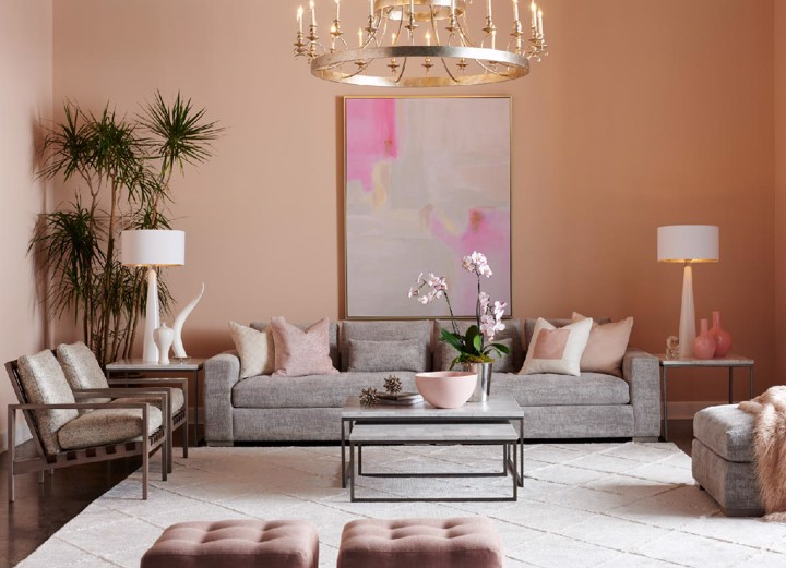 Grey upholstered sofa with arm chairs, rose colored ottomans and grey tufted ottoman