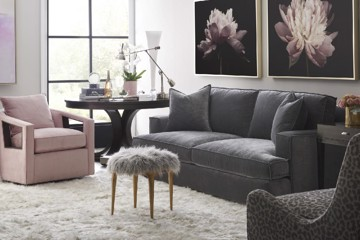 Pink upholstered arm chair with grey sofa and fur ottoman