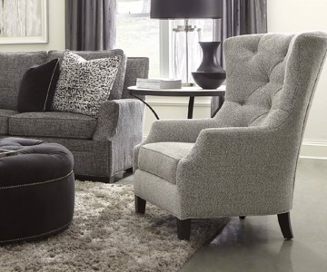 Ivory tufted upholstered high-back arm chair with tufted upholstered round ottoman