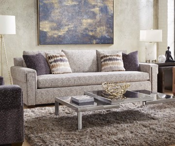 Beige upholstered sofa with tan leather wing-back chair