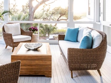 Woven loveseat and arm chair with white upholstered cushion and cocktail table