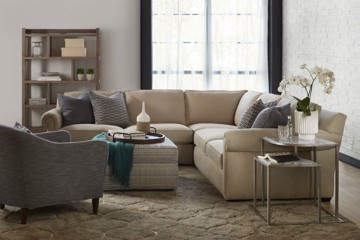 Sam Moore tan leather sofa, upholstered grey arm chair, and upholstered print ottoman