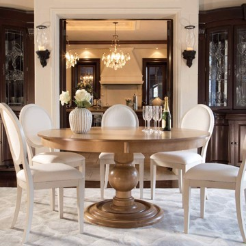 Round dining table with upholstered chairs in traditional style dining room