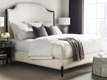 White upholstered bed with nail head trim and tufted ottoman